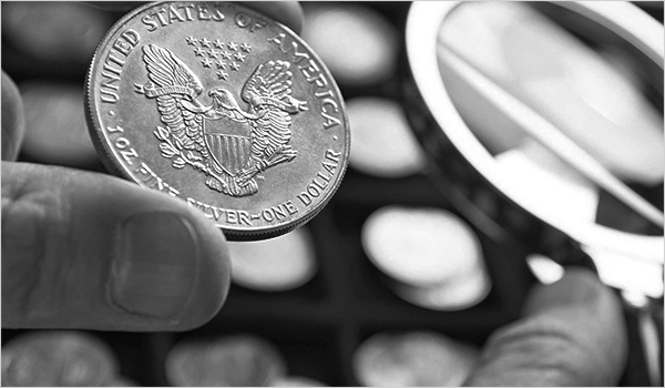 A coin grader checking a One Dollar US silver coin